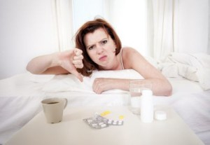 Angry woman with coffee and diarrhea medicine giving a thumbs down.