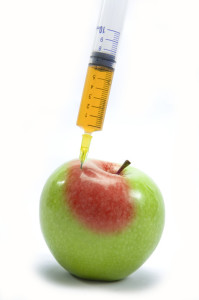 An apple with a syringe injecting NATURAL food additives.