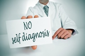 Doctor in a white lab coat holding a sign that says no self-diagnosis.