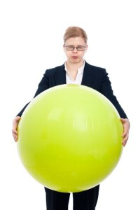 Businesswoman With Exercise Ball Like She Had a Bloated Belly