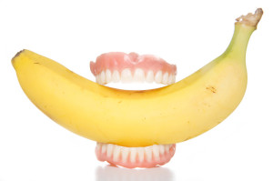 False teeth biting a banana