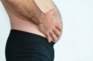 Man holding his big distended bloated belly.
