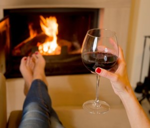 Woman relaxing with wine by the fire from solvingtheibspuzzle.com