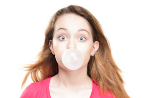 Wide eyed woman blowing a bubble with chewing gum.
