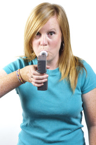 Woman blowing into a hydrogen breath test machine.