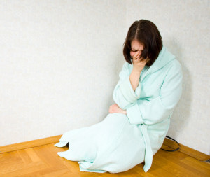 Woman sitting on the floor in the corner with depression anxiety and IBS