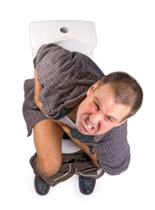 Man on the toilet, grimacing in pain.